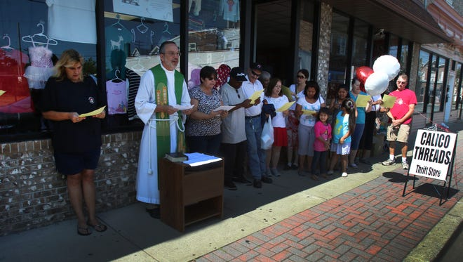 The Rev. Gregory Bezilla conducts a ceremony at Calico Threads Thrift Shop in South River.