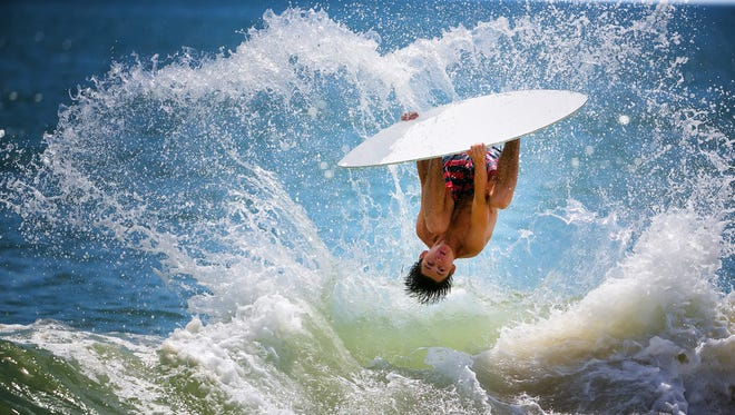 Carter Hill,16, flips over the waves doing a barrel roll during his practice session at Dewey Beach as he prepares to compete at The Zap World Championship of Skimboarding.