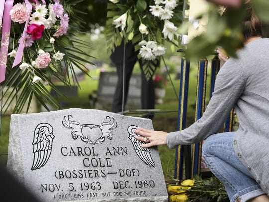 FILE PHOTO: A woman touches the headstone of Carol Ann Cole at Maple Grove Cemetery on Thursday, June 18, 2015, in Kalamazoo, Mich.