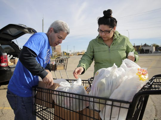 Robert Zizzo, Stock the Shelves Mobile Food Pantry volunteer and news director for the Green Bay Press-Gazette, helps Mayra Duran load her car during the mobile pantry Thursday, Oct. 19, 2017, in Appleton, Wis.