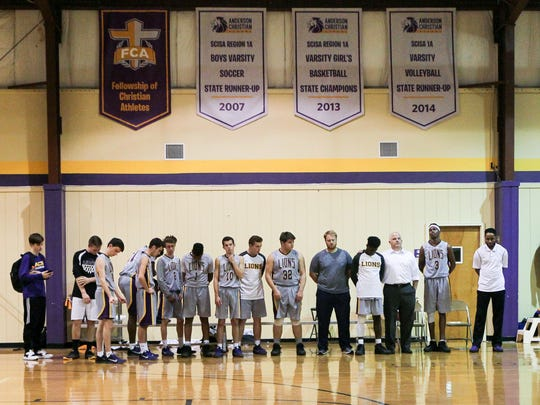 Brandon Young, right of players, coach of the Anderson Christian School Lions, joins in prayer under several basketball banners in the school gymnasium before tipoff with the Greenville Home School Hurricanes in Anderson. Young was a player with Anderson University until 2011.