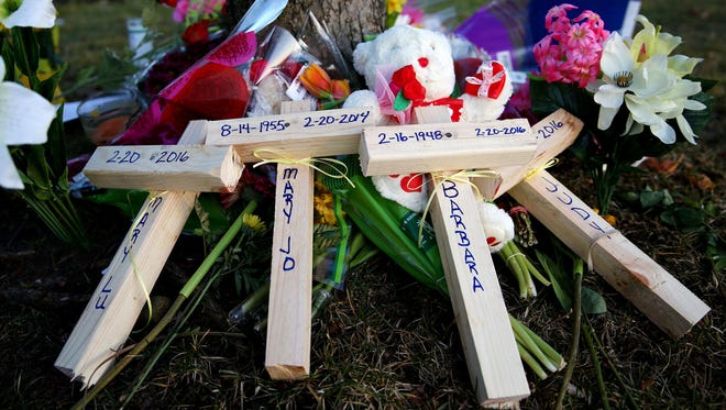 Crosses with the names of victims of a shooting spree rests by the side of a tree outside of the Cracker Barrel in Kalamazoo, Mich.