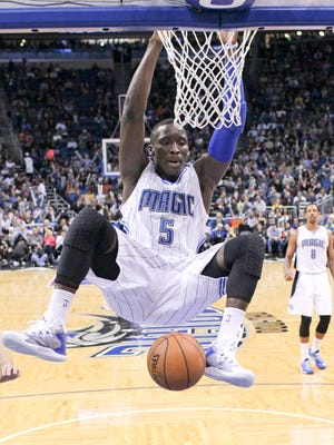 In this Jan. 16, 2015, file photo, Orlando Magic's Victor Oladipo (5) hangs on the rim after dunking the ball against the Memphis Grizzlies.
