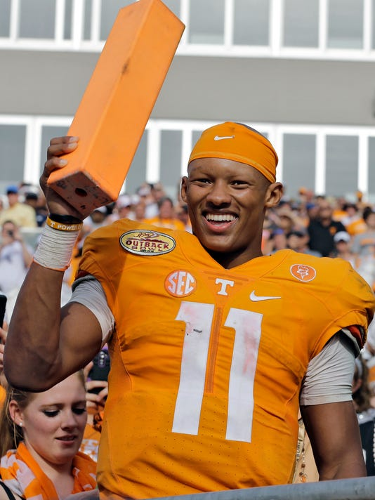FILE - In this Jan. 1, 2016, file photo, Tennessee quarterback Joshua Dobbs smiles as he holds a pylon after their 45-6 win over Northwestern in the Outback Bowl NCAA college football game, in Tampa, Fla. Teammates and coaches say they've noticed a difference in Tennessee quarterback Joshua Dobbs this year. The senior has become a more vocal leader and is making sure the No. 9 Volunteers are ready to deal with the high preseason expectations heading into Thursday's opener with Appalachian State. (AP Photo/Chris O'Meara, File)