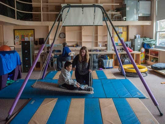 District occupational therapist Jenn Stell swings West End Elementary School fourth-grader Henderson Colindres during a session in the sensory room for students with autism and other disabilities at the Woodbury school.