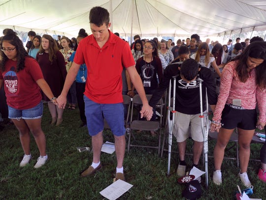 McMurry University students Tuesday join hands for a prayer during chapel. McMurry held the gathering under a tent and served lunch afterward.