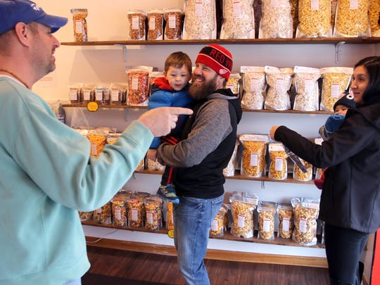 Jeff Anderson talks with the Jenkins family who stopped by to sample and shop at Greendale's The Popcorn Shoppe at 5632 Parking St.