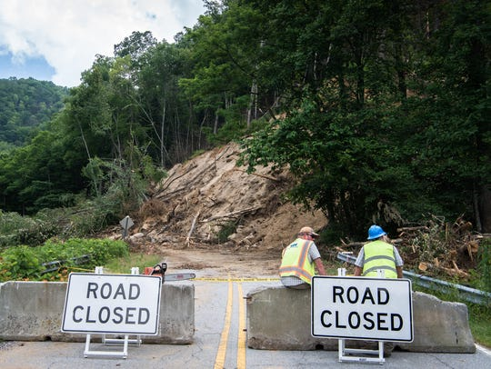 Workers take a break at the site of a landslide covering a 100-foot stretch of N.C. 9 near Bat Cave which occurred earlier this month during periods of heavy rainfall.