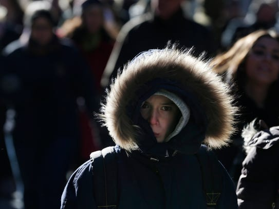 Pedestrians try to keep warm while walking in New York's