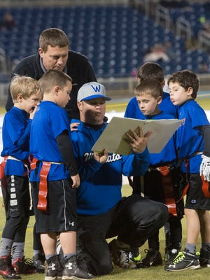 Flag football coach Dave Wilson, kneeling, gives his team a few pre-game instruction before Friday night's game at Blue Wahoos Stadium. Washington High School grad and NFL Hall of Famer, Derrick Brooks, is helping to sponsor the new youth league.