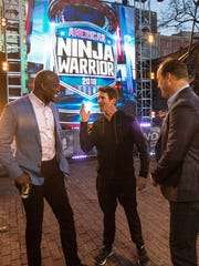 "IndyCar driver Scott Dixon, middle, talks with ""American Ninja Warrior"" hosts Akbar Gbaja-Biamila, left, and Matt Iseman, right, before his attempt on the course."