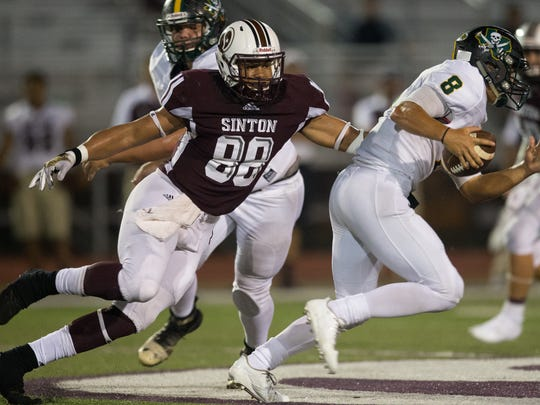 Rockport-Fulton's quarterback Will Smith runs the ball under presser from Sinton's Daryl French during the fourth quarter of their game at Pirates Stadium in Sinton on Friday, Sept. 8, 2017.
