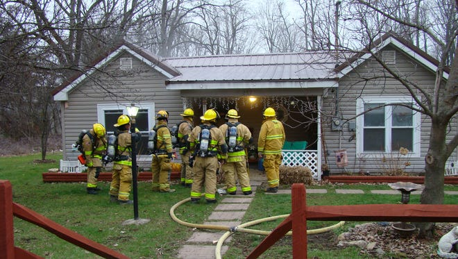 Bath firefighters stand outside a home on McMaster Street on Sunday after putting out a blaze.