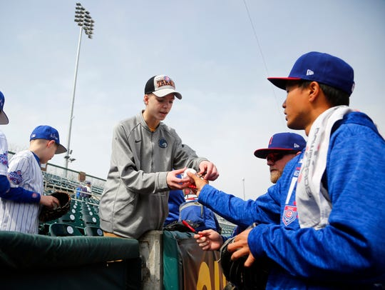 Pitcher Jen-Ho Tseng signs a ball for Zach Niederklopfer,