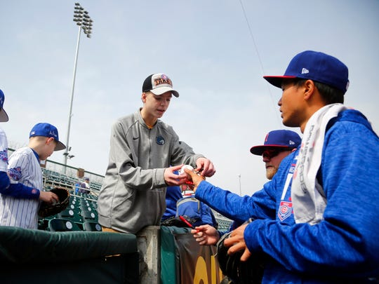 Pitcher Jen-Ho Tseng signs a ball for Zach Niederklopfer, 14, of Ankeny before the Iowa Cubs home opener Thursday, April 5, 2018.