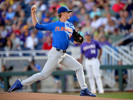 FILE - In this June 26, 2017, file photo, Florida pitcher Brady Singer (51) throws in the first inning of Game 1 of the NCAA College World Series baseball finals against LSU, in Omaha, Neb. The defending national champion Gators are No. 1 in every major preseason poll. Five everyday starters are back, and the pitching rotation is headed by projected first-round picks Brady Singer and Jackson Kowar. (AP Photo/Matt Ryerson, FIle)