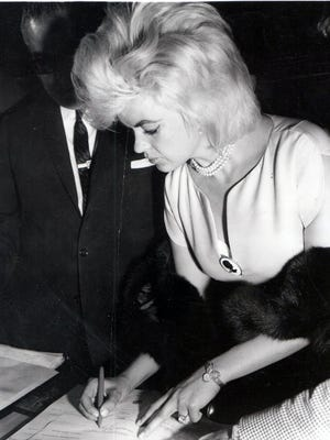 Blonde actress Jayne Mansfield is shown signing her divorce petition in 1963 against her husband, Mickey (Miklos) Hargitay in the office of the Juárez city attorney. Several minutes later, the actress walked out of the First Civil Court with a divorce on grounds of incompatibility.