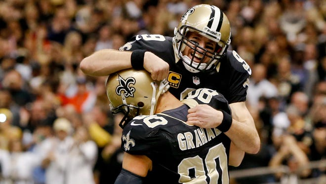 New Orleans Saints quarterback Drew Brees (9) celebrates with  tight end Jimmy Graham (80) following a touchdown against the Tampa Bay Buccaneers at the Mercedes-Benz Superdome in New Orleans on Dec. 29, 2013.