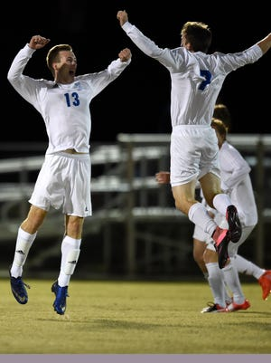 Andrew Cross (13) of Memorial celebrates with teammate Henry Kinkel(7) after after Cross scored the first goal of the game against Castle during the first half of the Class 2A boys' soccer sectional championship match at Traylor Family Stadium in Evansville Saturday.  Memorial won the championship 2-1.