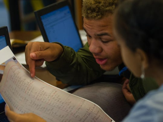 Tanderious Williams, 16, of Nashville leans over to help Hermela Demma, 17, of Antioch figure out what one of the library's original book ledgers says as they work at the Special Collections Library at Vanderbilt on Monday, June 12, 2017. The three high school students employed by the Vanderbilt library through Opportunity NOW are working to find the original books of the library.