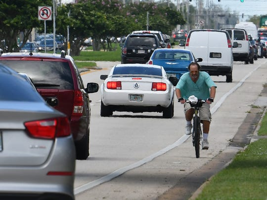A man riding a bike against traffic on E. New Haven Avenue in Melbourne,