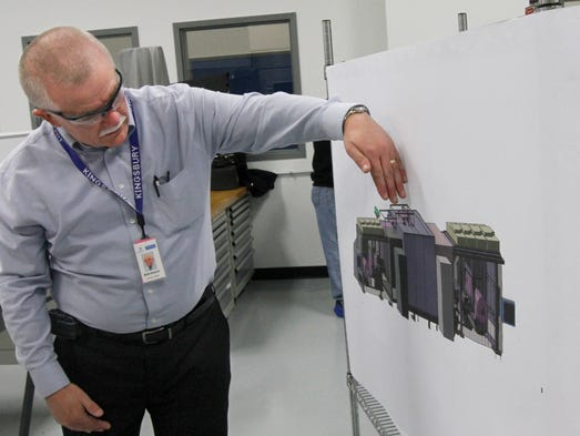 Bob Smarcz, engineering manager at Kingsbury Corp. on Lexington Ave. in Rochester, explains how special rolls of Kodak film are run through a exposure machine, printing touchscreens on both sides of the film.  The film is flash exposed, processed and dried completely in the dark before moving into the light for the final stage of sensor testing.