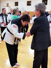 Jill Carlson is awarded her new belt by Master Linda