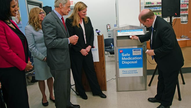 Sen. Chris Coons demonstrates how to discard old prescription drugs in a box at the Walgreens in Fairfax Shopping Center after announcements for Drug Take-Back Day on April 29th.