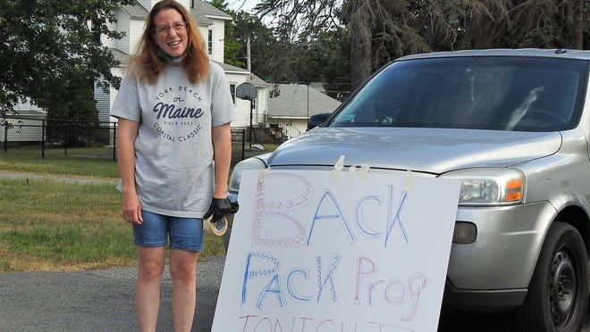 Deirdre Holt hands out the first of the food for the summer backpack program at Immaculate Heart of Mary Church in Winchendon.