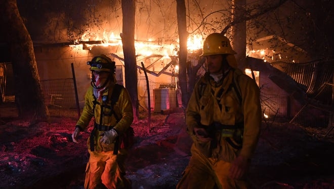 Firefighters move away from a burning house after discovering downed live power lines, as the Thomas wildfire continues to burn in Carpinteria, Calif. on Dec. 10, 2017.