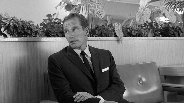 """Actor Charlton Heston takes a break in Milwaukee on July 13, 1965. He was traveling with his family to New York, London and eventually Egypt, where he was to begin shooting the adventure movie """"Khartoum."""""""