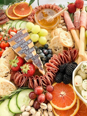 Charcuterie boards from The Gift of Charcuterie include breads, crackers, meats, cheeses and fresh produce.