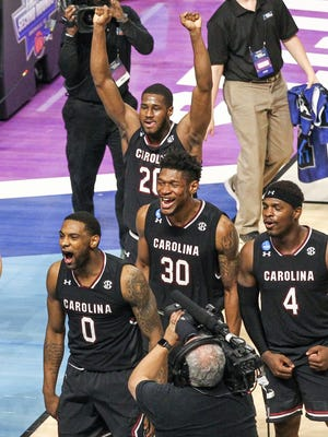 South Carolina guard Sindarius Thornwell, left, forward Chris Silva (30) and guard Rakym Felder (4) celebrate a win during the NCAA Tournament at Bon Secours Wellness Arena in downtown Greenville on Sunday, March 19, 2017.