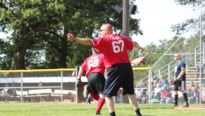 Lt. Jb Moody waves runners around the bases during the first Guns n' Hoses charity softball game.