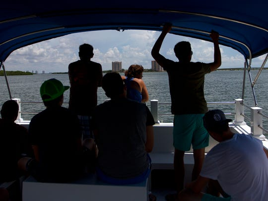 Tourists look for dolphins recently during a cruise led by Good Time Charters Dolphin Cruises.