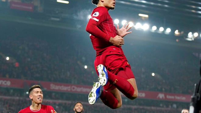 Liverpool's Virgil van Dijk jumps to celebrate scoring his side's first goal during the English Premier League soccer match between Liverpool and Manchester United at Anfield Stadium in Liverpool, Sunday, Jan. 19, 2020.