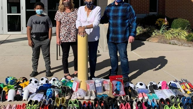 Donations of soccer items for children in Africa filled the sidewalk at Keyser Primary School as (l-4) Little Dude Zavon Evans, Keyser Primary Principal Lisa Goldstrom, Grandma Suellen Clay and Dean Richardson of Potomac State College prepared them for shipping. Photos courtesy Aubrey Stewart Project