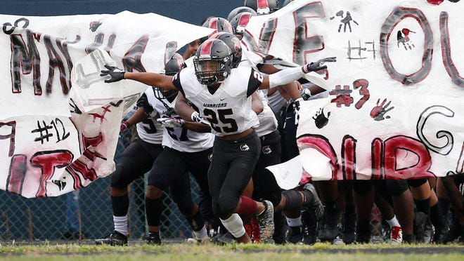 Harvest Prep's Shaun Goines leads his team onto the field before last year's season opener against Eastmoor Academy. High school teams are practicing now in anticipation of a season that may be impacted even more than it already has been by the coronavirus.