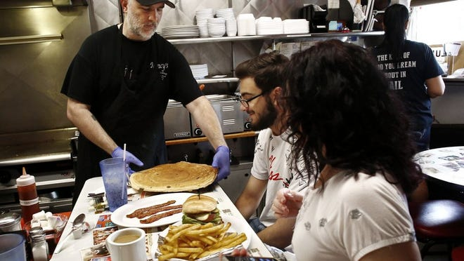 Rick Hahn, left, at the old Nancy's Home Cooking in Clintonville. Hahn has reopened the diner in Downtown's Lynn Alley.