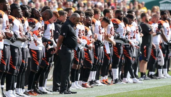 The Cincinnati Bengals lock arms during the national
