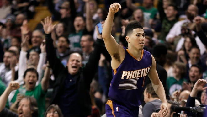 Phoenix Suns guard Devin Booker gestures after he scored a basket, as fans cheer him at TD Garden in the fourth quarter of the Suns' NBA basketball game against the Boston Celtics, Friday, March 24, 2017, in Boston. Booker scored 70 points, but the Celtics wonp 130-120. Booker is just the sixth player in NBA history to score 70 or more points in a game.