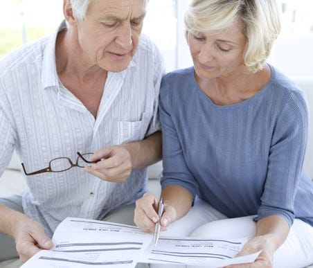 Senior couple reviewing documents while sitting on couch
