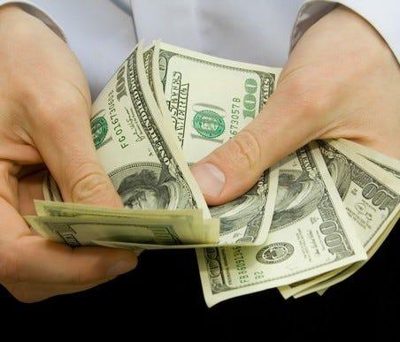 Man counting 100-dollar bills