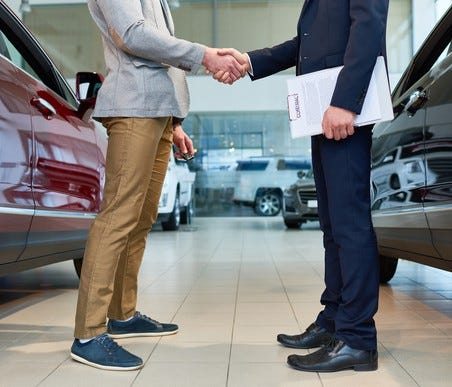 A car dealer makes a sale.