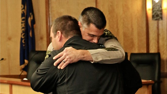 Sheriff Jason Myers embraces deputy James Buchholz, the recipient of the Purple Heart award.