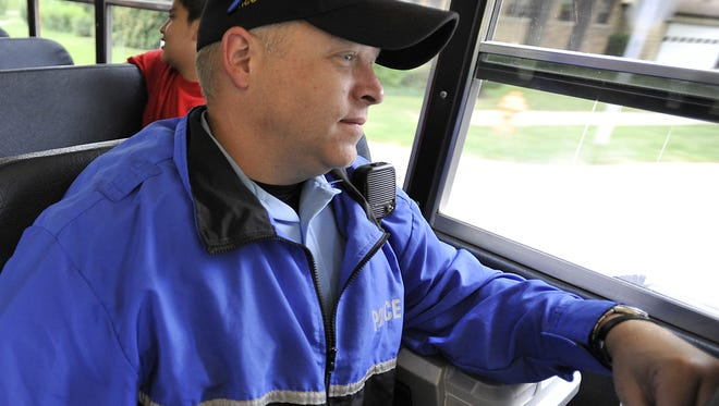In this photo, dated Sept. 8, 2011, Lansing Police officer John Chamberlin rides a Lansing school bus to watch for drivers committing traffic violations around the buses.