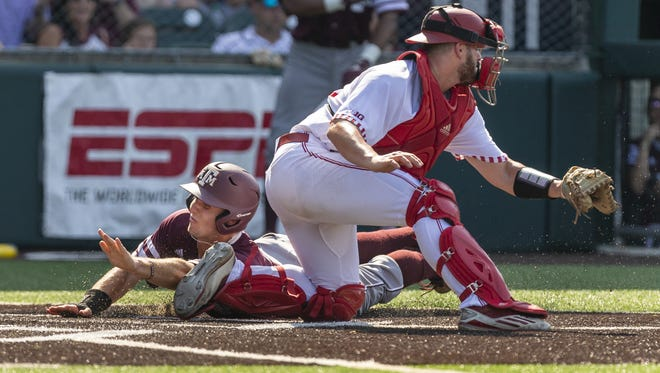 Texas A&M's Zach DeLoach scores past Indiana's Ryan Fineman during an NCAA Austin Division I Regional game at Disch-Falk Field in Austin, Texas, Friday, June 1, 2018.