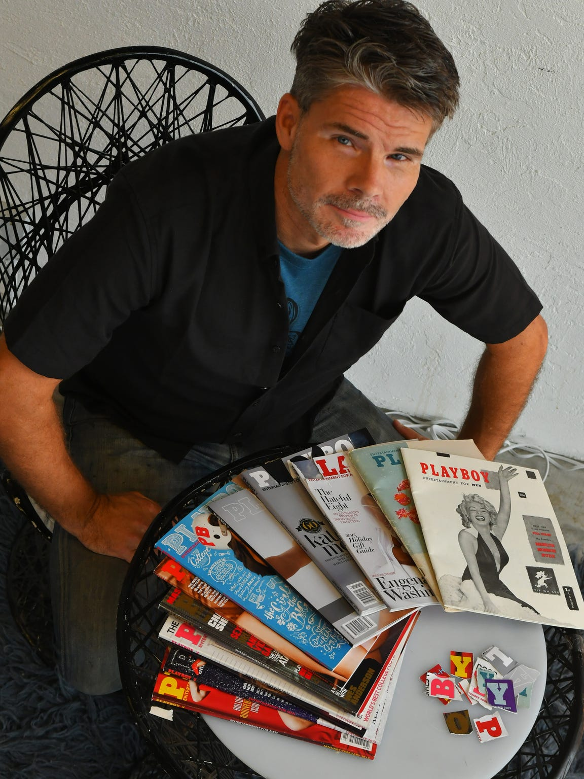 Derek Gores poses with Playboy issues in his Eau Gallie gallery.