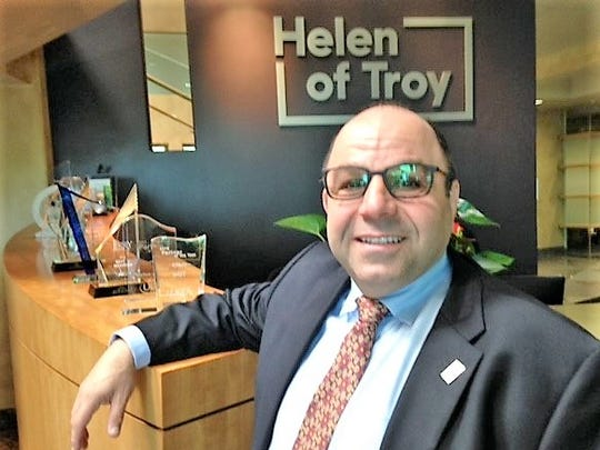 Helen of Troy CEO Julien Mininberg stands in the lobby of the El Paso company's headquarters with its new logo behind him.