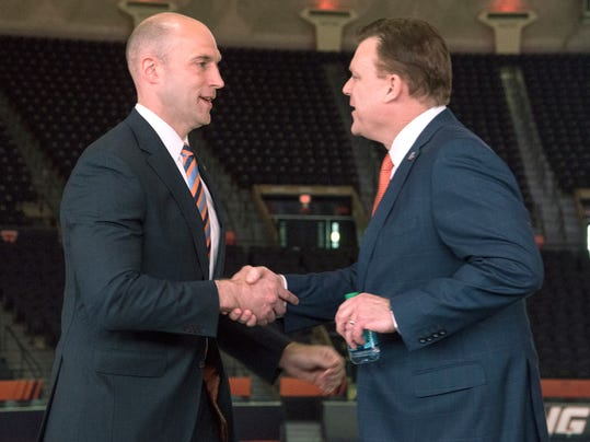Illinois athletic director Josh Whitman, left, shakes hands with newly hired men's basketball coach Brad Underwood during a news conference in Champaign, Ill., Monday, March 20, 2017. (John Dixon/The News-Gazette via AP)